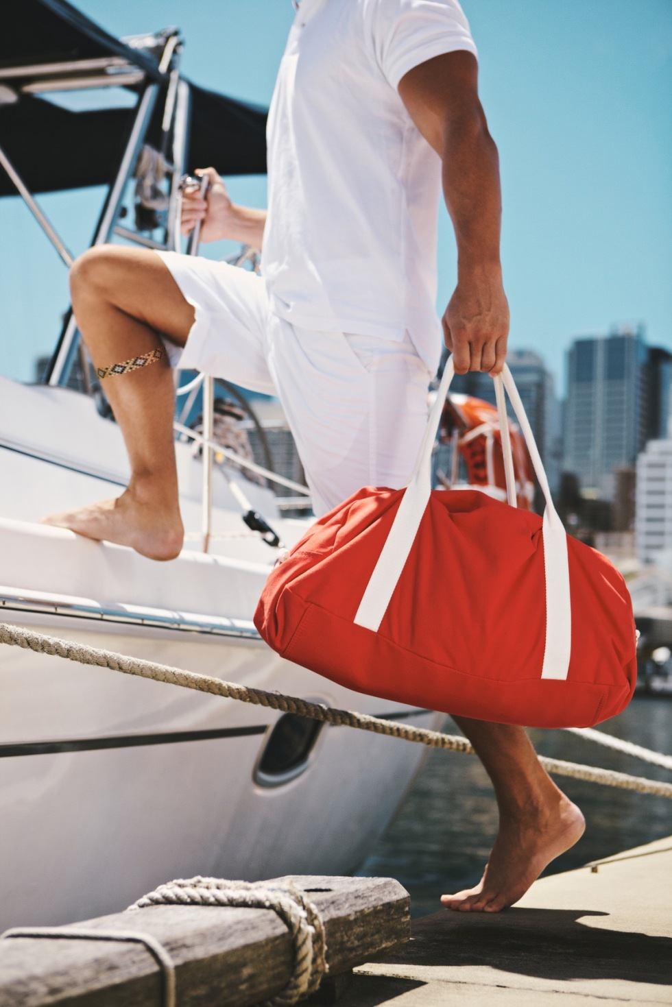 Young man getting in boat holding luggage in hand